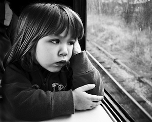 A bored child staring out of a train window.